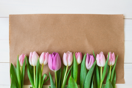 Bouquet of beautiful fresh tulips with craft paper on the wooden background. Copy space.