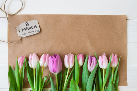 Womens day. beautiful fresh tulips with paper on the wooden background.