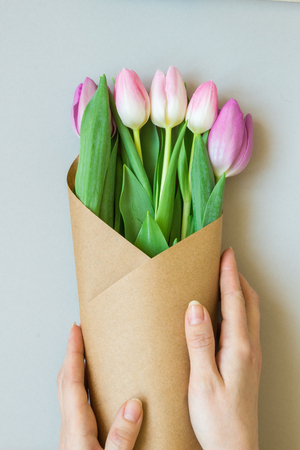 Hands holding bouquet of beautiful pink and purple fresh tulips. 版權商用圖片