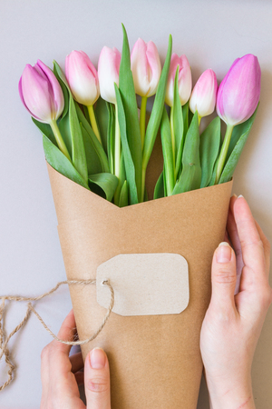 Hands holding bouquet of beautiful pink and purple fresh tulips with card. 版權商用圖片