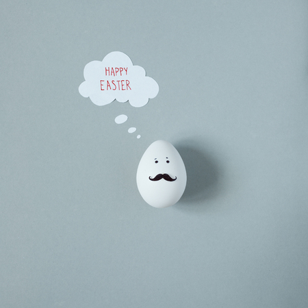 Happy Easter. Funny easter egg with mustache on gray background.