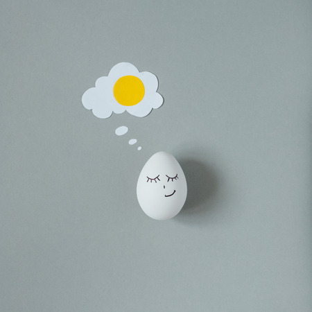 Smiling egg with fried egg made of thought bubble on gray background.