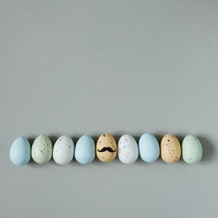 Happy Easter. Funny easter eggs with mustache on gray background. Copy space