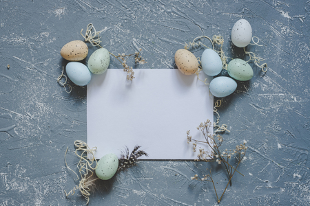 Happy easter. Easter eggs with white sheet of paper, top view. Copy space. 版權商用圖片