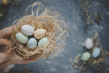 Happy easter. Hands holding easter eggs in nest with easter decoration, top view. Selective focus