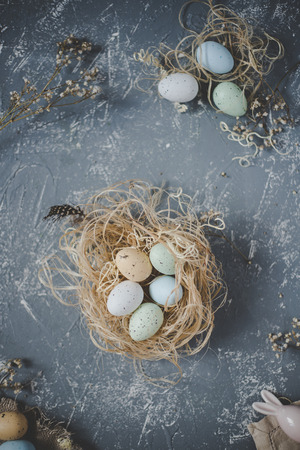 Happy easter. Easter eggs in nest with easter decoration, top view.