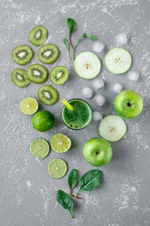 Healthy green smoothie with fresh green fruits and spinach leaves on gray background, top view Фото со стока