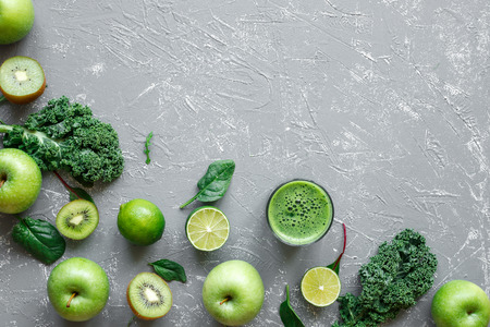 Healthy green smoothie with ripe green fruits, kale and spinach on gray background, top view