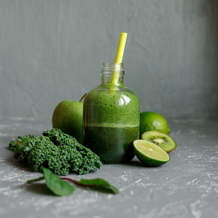 Healthy green smoothie with kale, apple, spinach, lime and kiwi on gray background
