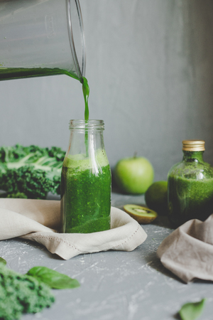 Hands pouring healthy green smoothie in a jar. Clean eating concept. Фото со стока