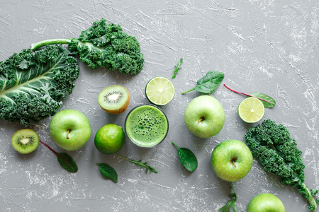 Healthy green smoothie with ripe green fruits, kale and spinach on gray background, top view. Stock Photo