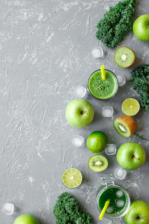 Healthy green smoothie with fresh green fruits, kale and spinach on gray background, top view. Фото со стока