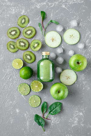 Healthy green smoothie with fresh green fruits and spinach leaves on gray background, top view.