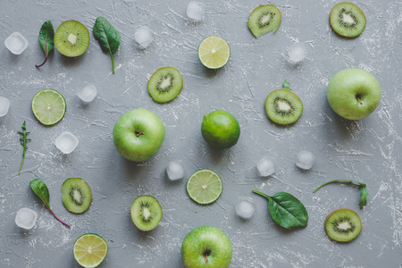 Fresh green fruits with spinach leaves and ice cubes on gray background top view.