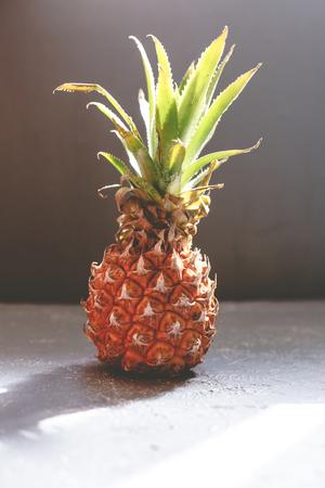 Ripe juicy pineapple on gray wooden table, backlight. Фото со стока