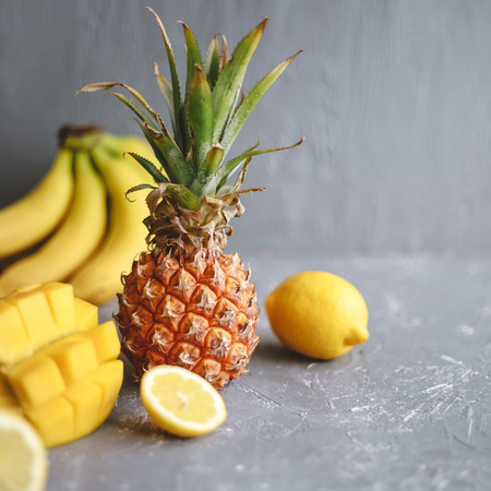 Yellow fruits. Ripe juicy pineapple with mango, banana and lemons on gray wooden table