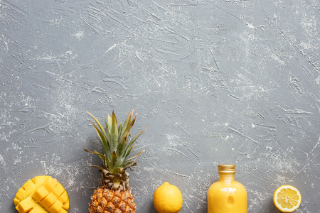 Fresh yellow smoothie with pineapple, mango and lemons on gray table, top view. With copy space.