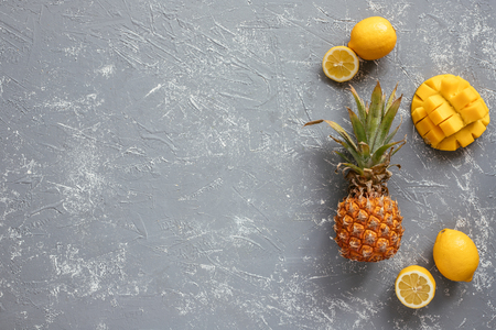 Yellow fruits. Ripe juicy pineapple with mango and lemons on gray wooden table, top view. With copy space Stock Photo
