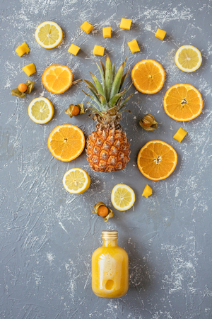Sweet yellow smoothie with pineapple, citrus and yellow fruits on gray wooden table, top view.