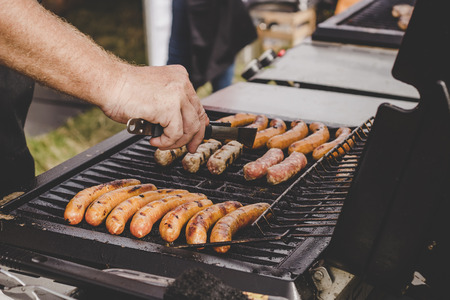 Grilling delicious juicy meat sausages on big grill outdoor. Фото со стока