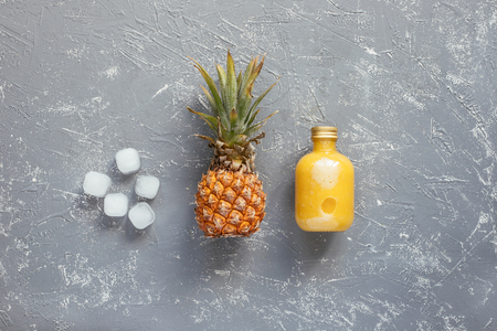 Refreshing yellow smoothie with pineapple and ice cubes on gray wooden table, top view.