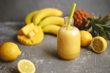 Fresh yellow smoothie with lemons, banana and pineapple on gray background Stock Photo