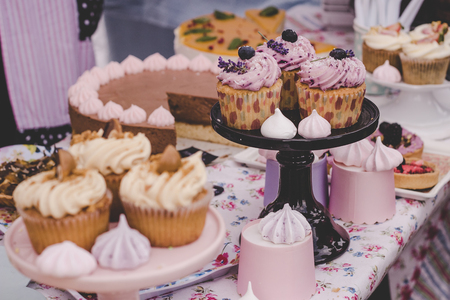 Delicious cupcakes with cream cheese frosting, candies and meringues. Фото со стока