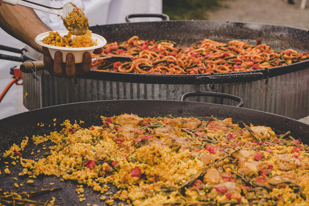 Traditional paella with chicken and vegetables at street food market.