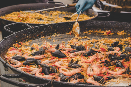 Traditional paella with sea food and vegetables at street food market. Stock Photo