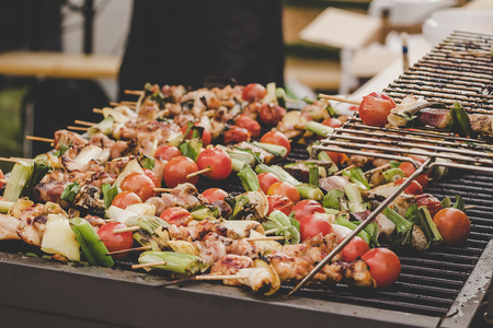 Grilled delicious kebab with meat and vegetables at street food market.