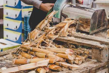 Man queezing sugar cane juice at street food market.