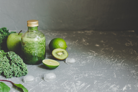 Healthy green smoothie with ingredients and ice cubes on gray background. Copy space Фото со стока