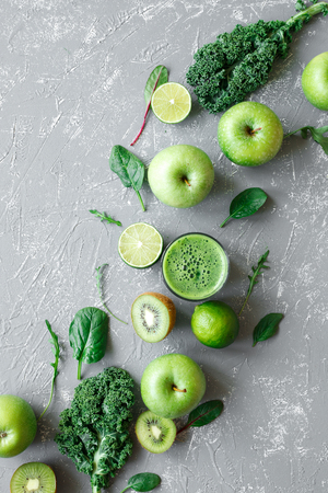 Healthy green smoothie with fresh green fruits, kale and spinach on gray background, top view. Stock Photo
