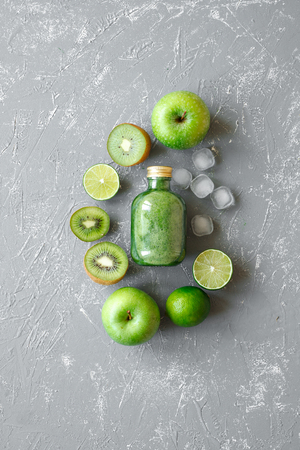 Healthy green smoothie with fresh green fruits and ice cubes on gray background, top view.