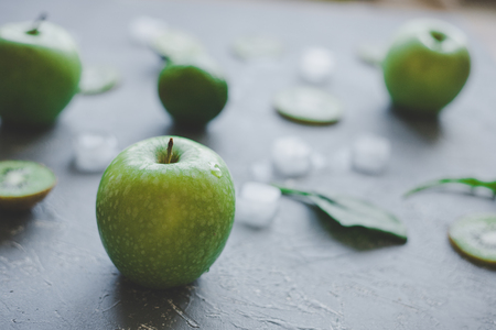 Ripe green apple on rustic table with green fruits and ice cubes, selective focus.