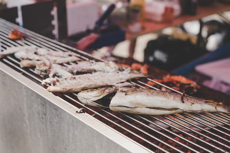 Grilled fish on the grill at street food market, selective focus. Stock Photo