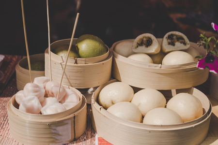 Asian steamed buns in bamboo steamers at street food market. Фото со стока