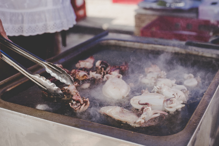 Grilling delicious seafood at street food market.