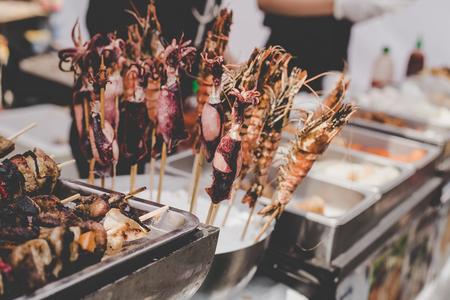 Grilled prawn and squid skewers at street food market, selective focus.