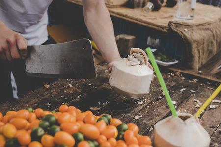 Man cutting fresh coconut at street food market. Фото со стока