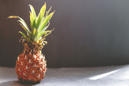 Ripe juicy pineapple on gray wooden table, backlight. With copy space