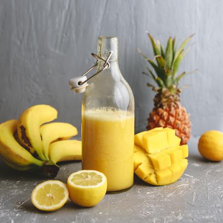 Refreshing yellow smoothie with lemons, banana, mango and pineapple on gray background.
