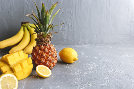 Yellow fruits. Ripe juicy pineapple with mango, banana and lemons on gray wooden table. Copy space