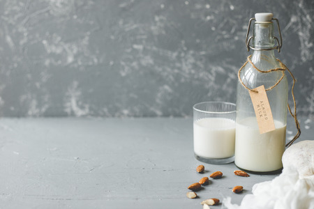 Vegan almond milk in glass bottle with almonds on wooden background with copy space.