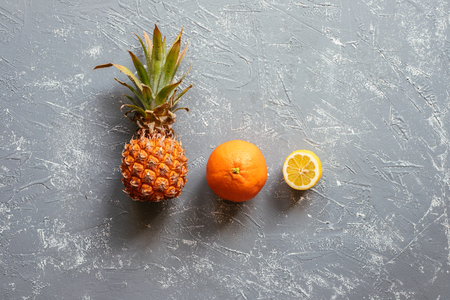 Ripe juicy pineapple with orange and lemon on gray wooden table, top view