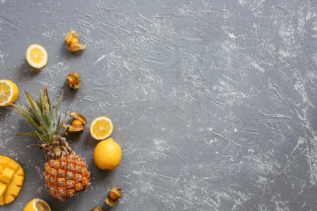 Yellow fruits. Ripe juicy pineapple with mango, physalis and lemons on gray wooden table, top view.