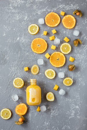Sweet yellow smoothie with yellow fruits on gray wooden table, top view.