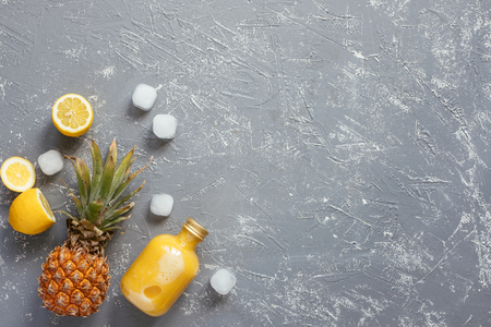Refreshing yellow smoothie with pineapple and ice cubes on gray wooden table, with copy space.