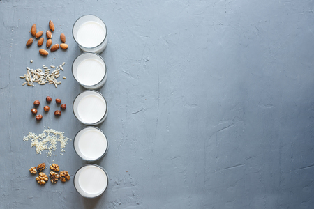 Different types of vegan non-dairy milk in glasses on wooden background with copy space. Top view.