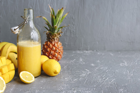 Refreshing yellow smoothie with yellow fruits and copy space on gray background.